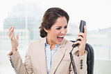 Outraged businesswoman shouting at phone