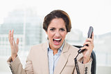 Furious businesswoman looking at camera and holding phone