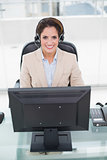 Happy businesswoman sitting in front of computer