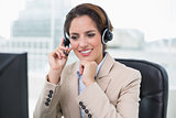 Cheerful businesswoman touching headset