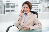 Smiling businesswoman calling with smartphone