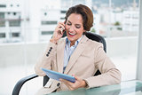Brunette laughing businesswoman using smartphone and holding tablet