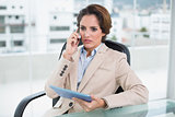 Frowning businesswoman on a call holding tablet