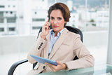 Frowning businesswoman using smartphone