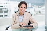 Smiling businesswoman using calculator