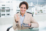 Smiling businesswoman holding calculator and giving thumb up