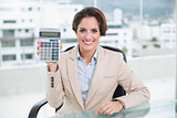 Cheerful businesswoman showing calculator