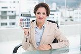 Unhappy businesswoman holding calculator