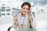 Worried businesswoman holding calculator