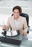 Businesswoman using calculator and diary smiling at camera