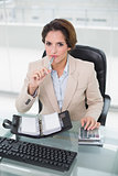 Thoughtful businesswoman using calculator and diary looking at camera