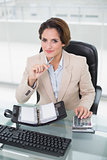 Smiling businesswoman using calculator and diary looking at camera