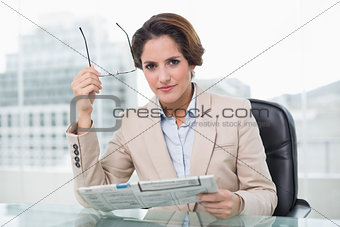 Focused businesswoman holding newspaper