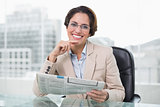 Businesswoman holding newspaper at her desk