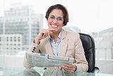 Businesswoman holding newspaper at her desk