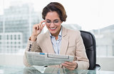 Smiling businesswoman reading newspaper at her desk