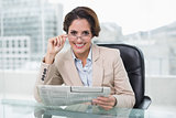 Smiling businesswoman holding newspaper at her desk
