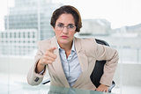 Angry businesswoman pointing at camera