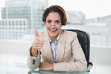 Cheerful businesswoman showing thumb up at her desk