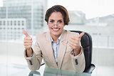 Happy businesswoman showing thumbs up at her desk