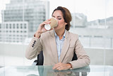 Happy businesswoman sitting at her desk drinking from disposable cup