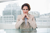 Cheerful businesswoman looking at camera at her desk