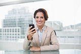Businesswoman smiling and holding her smartphone