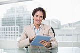 Businesswoman smiling and holding her tablet pc