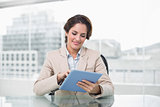 Businesswoman smiling and using her tablet pc