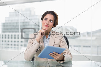 Thoughtful businesswoman smiling and using her digital tablet