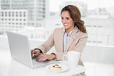 Happy businesswoman using laptop at her desk and having coffee