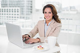 Cheerful businesswoman using laptop at her desk and having coffee
