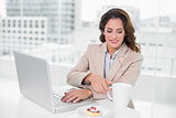 Cheerful businesswoman using laptop at her desk and having a coffee