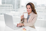 Cheerful businesswoman using laptop at her desk and holding mug