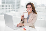 Smiling businesswoman using laptop at her desk and holding mug