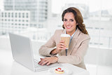 Businesswoman drinking coffee at her desk using laptop smiling at camera