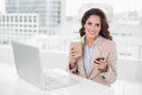 Cheerful businesswoman holding disposable cup and smartphone