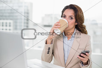 Attractive businesswoman drinking from disposable cup
