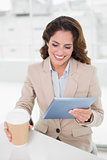 Happy businesswoman using digital tablet at her desk holding disposable cup