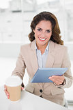 Smiling businesswoman using digital tablet at her desk holding disposable cup