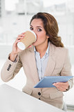 Smiling businesswoman using digital tablet at her desk drinking from disposable cup