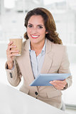 Cheerful businesswoman using digital tablet at her desk holding disposable cup
