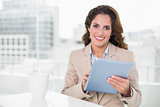 Beautiful cheerful businesswoman using tablet