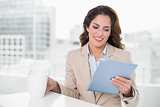 Beautiful content businesswoman using tablet