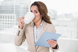 Businesswoman using tablet drinking coffee looking at camera