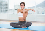 Sporty cheerful brunette stretching on exercise mat