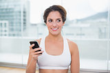 Sporty happy brunette holding smartphone