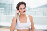 Sporty cheerful brunette phoning