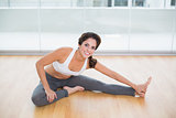 Sporty cheerful brunette stretching on the floor