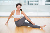 Sporty attractive brunette stretching on the floor
